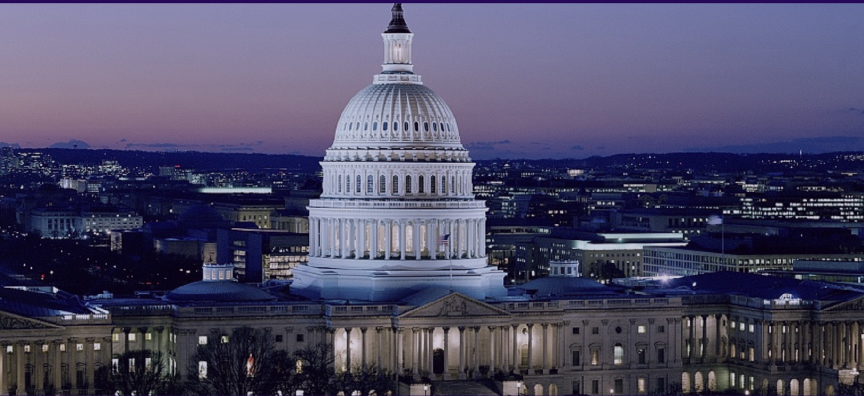 A photo of the U.S. Capitol at twilight, with a purple-blue gradient sky.