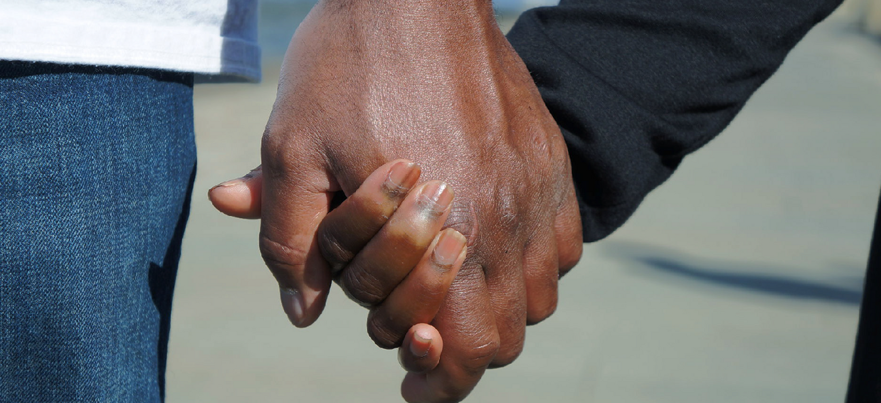 A close-up photo of a small Black hand clasped in a larger Black hand.