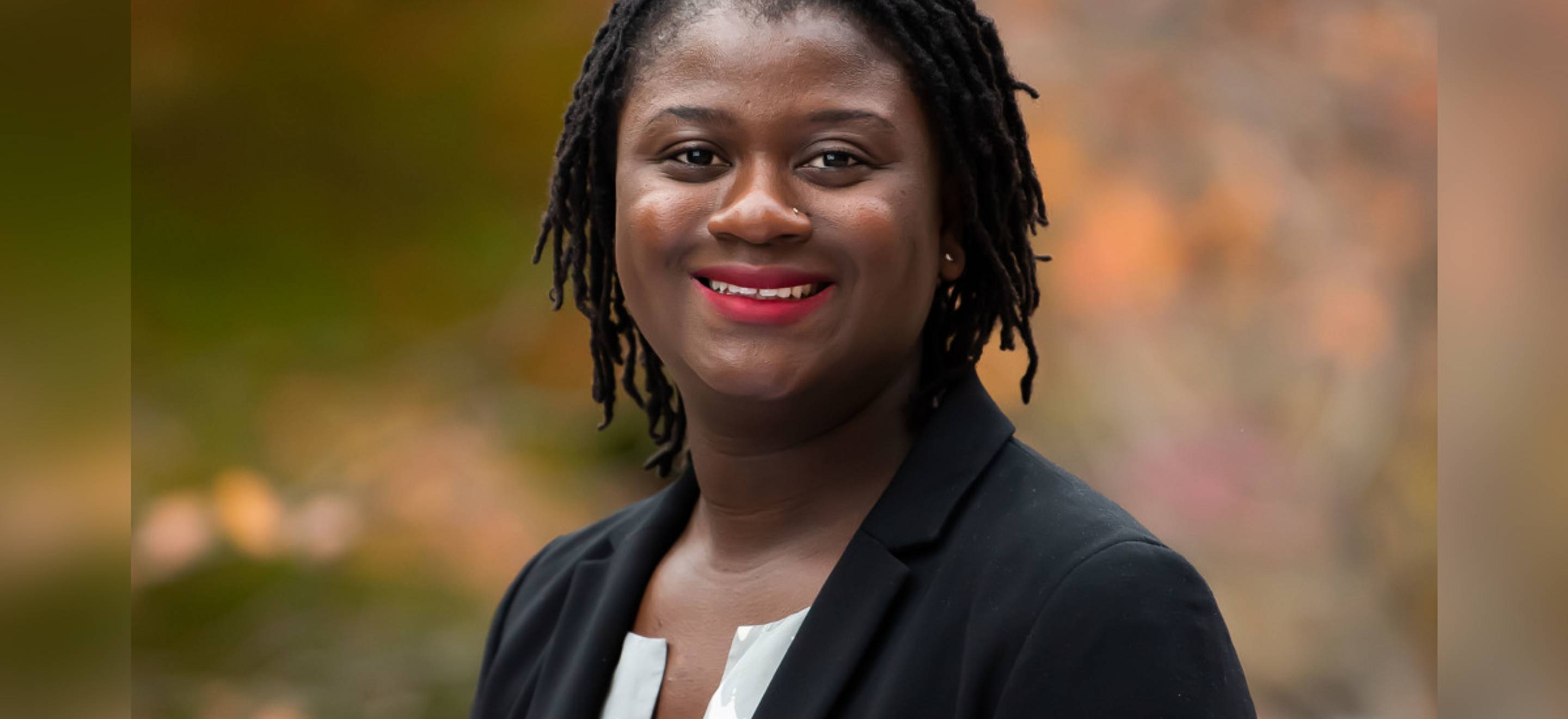 A headshot of IRAP alumna Samah Sisay. She is a Black woman wearing a black blazer and bright red lipstick, smiling brightly.