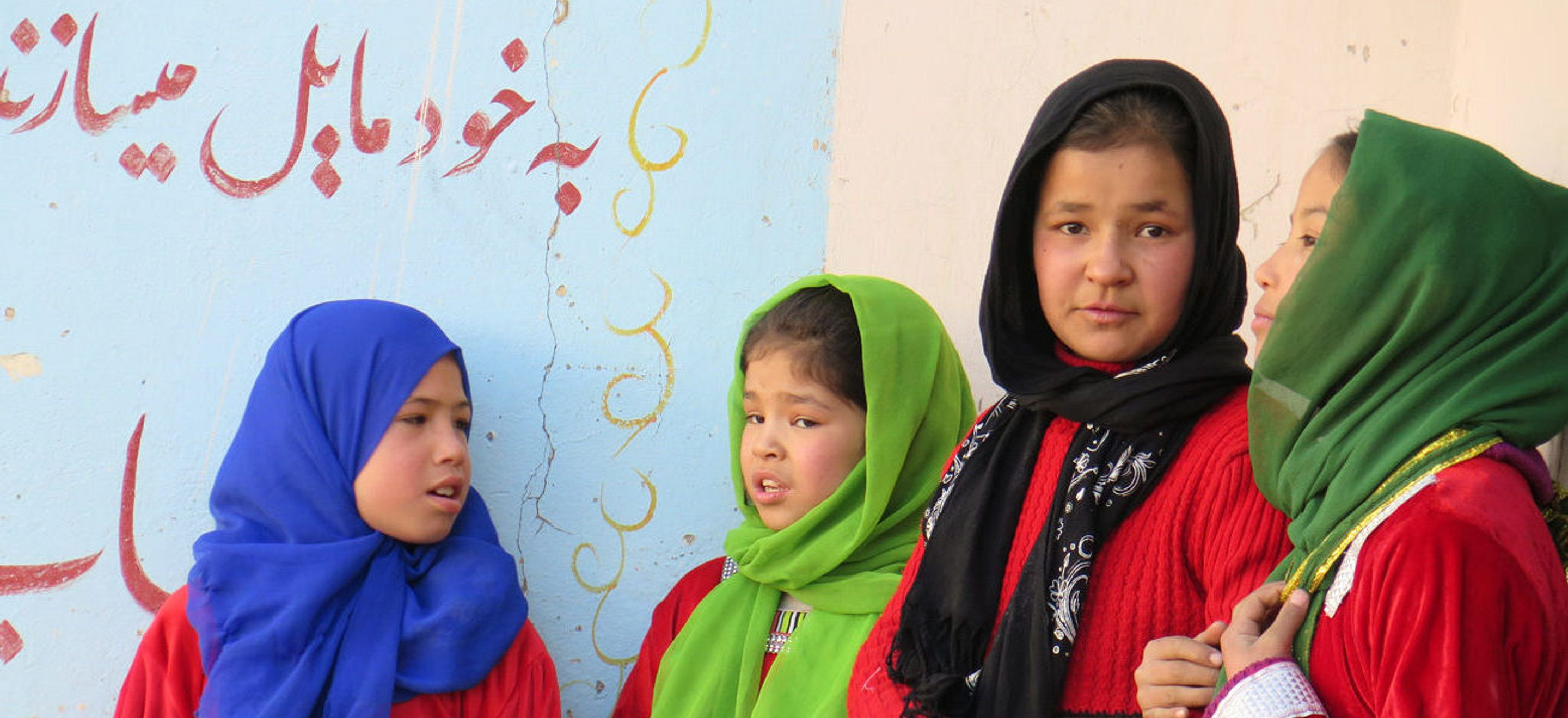 Four school-age girls in colorful headscarves and red dresses stand together against a colorful wall.