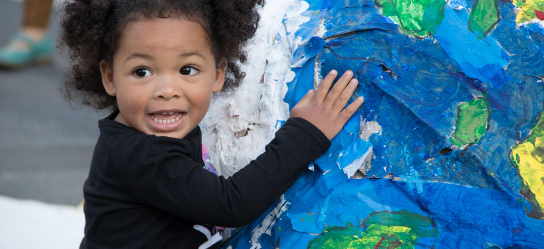 A photo of a young Black child hugging a papier mache globe.