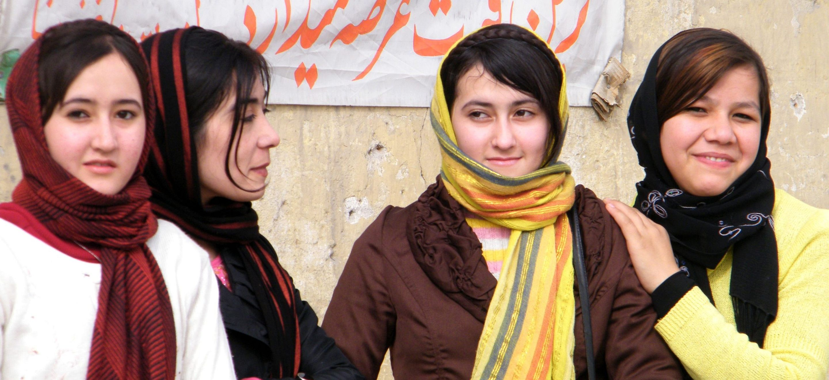 Four young Afghan women stand together linking arms and leaning on each other. Each women wears a striped headscarf.