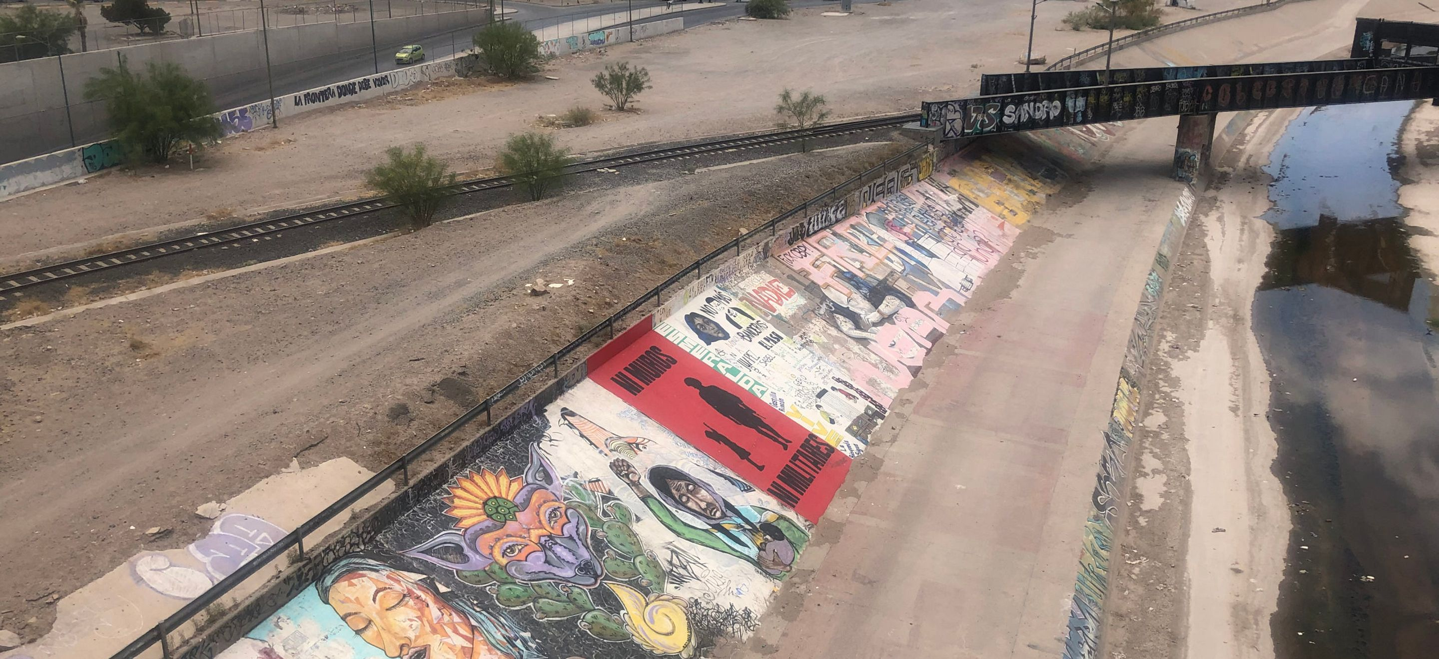 A photo from above a bank of political and cultural mural artwork. The artwork covers a sloped wall under a railway overpass.