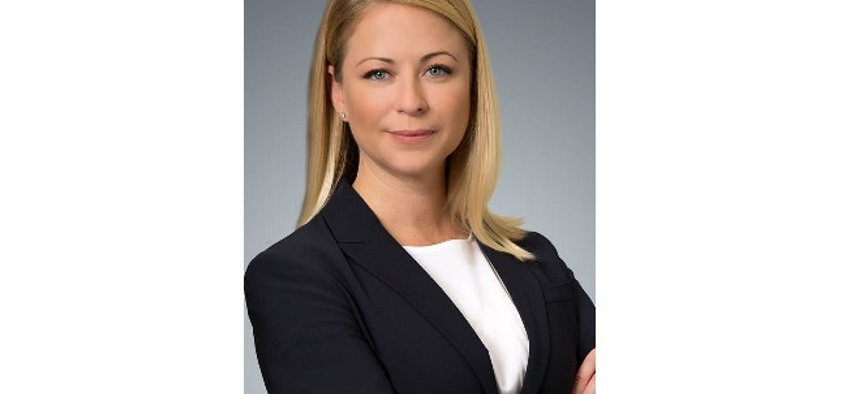 A headshot of IRAP alumna Alexis Federico. She is a white woman with straight blonde shoulder-length hair and blue eyes. She wears a white blouse with a black suit jacket and has her arms crossed in front of her.