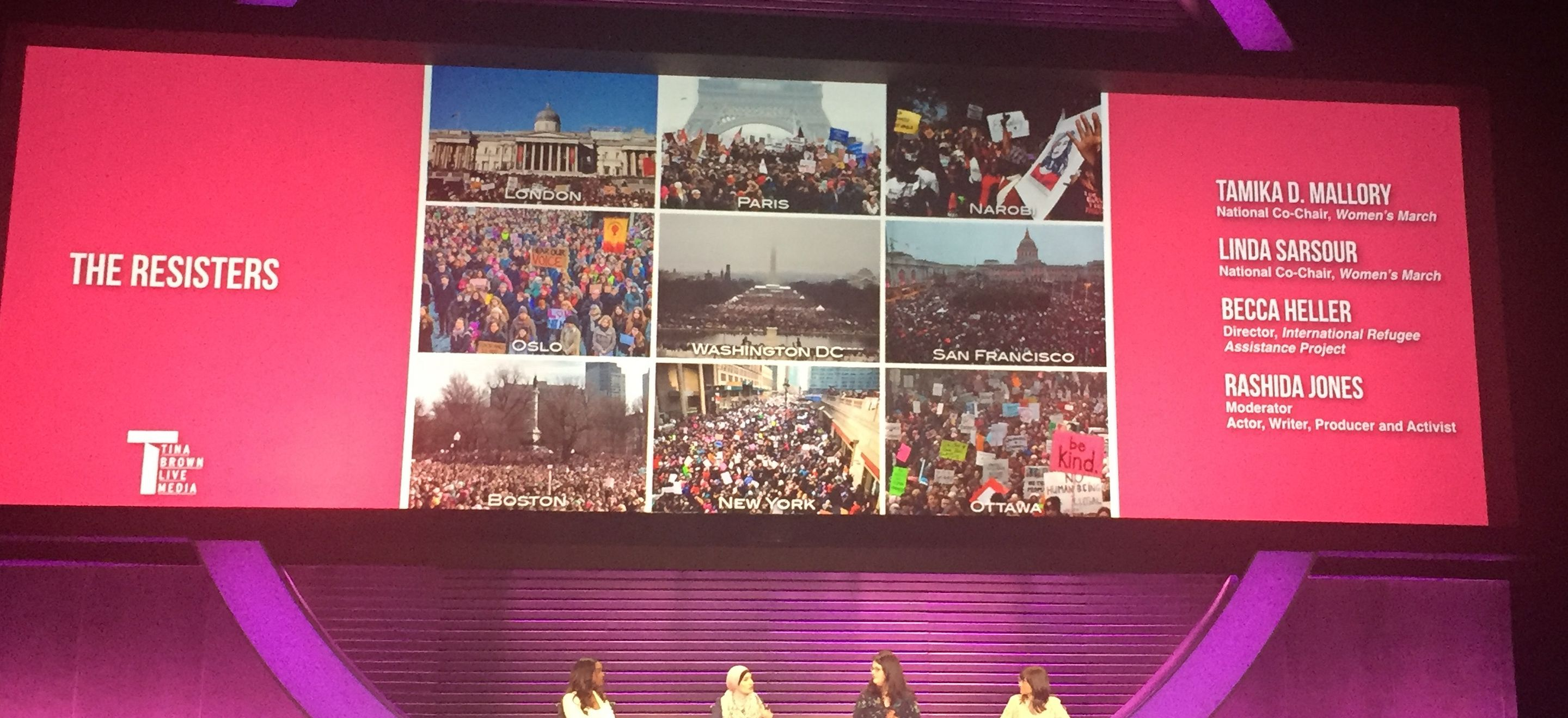 """Tamika D. Mallory, Linda Sarsour, Becca Heller, and Rashida Jones are seated in chairs on a stage. Behind them is a large screen displaying their names, images of protests across the world, and the words """"THE RESISTERS."""""""
