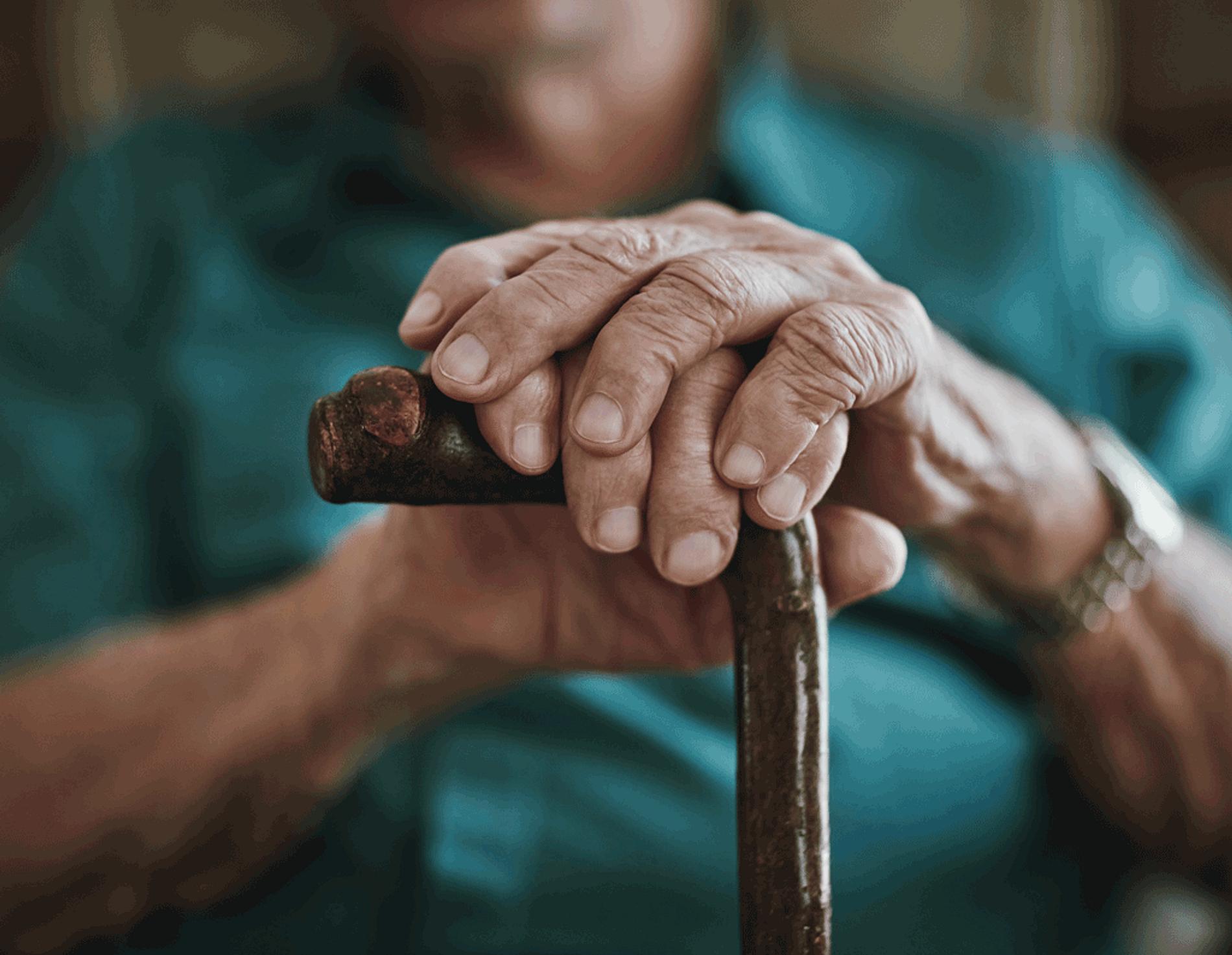Older gentleman's hands resting on a cane