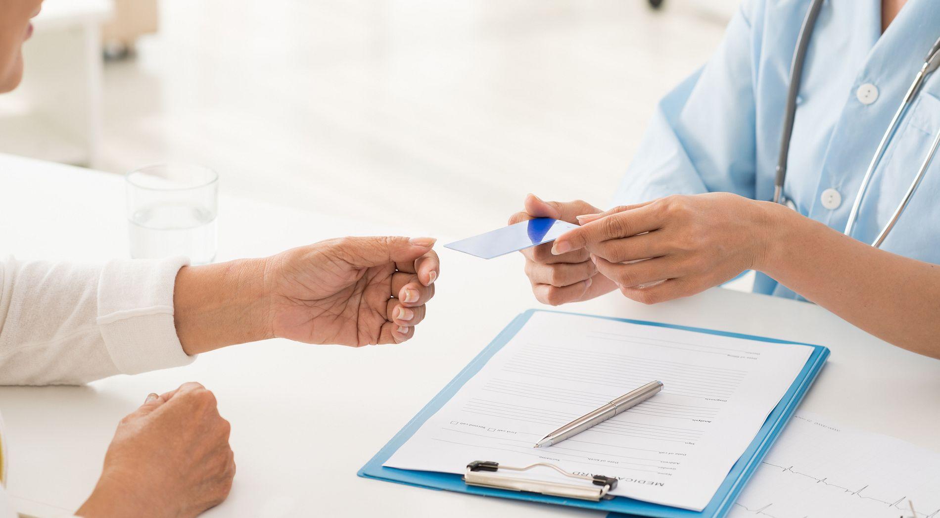 Nurse handing a card to a patient