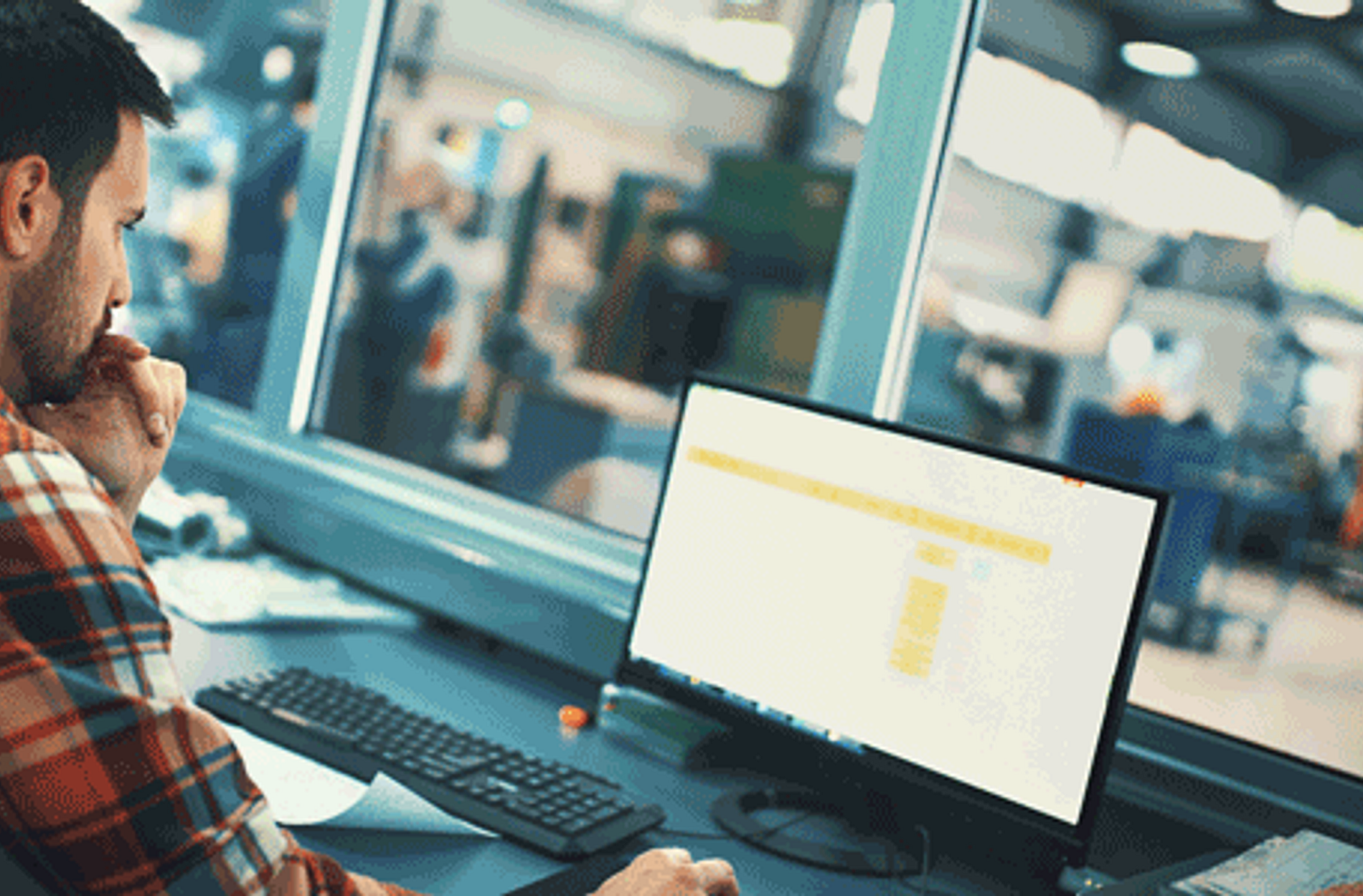 Man sitting at a manufacturing desk on a computer