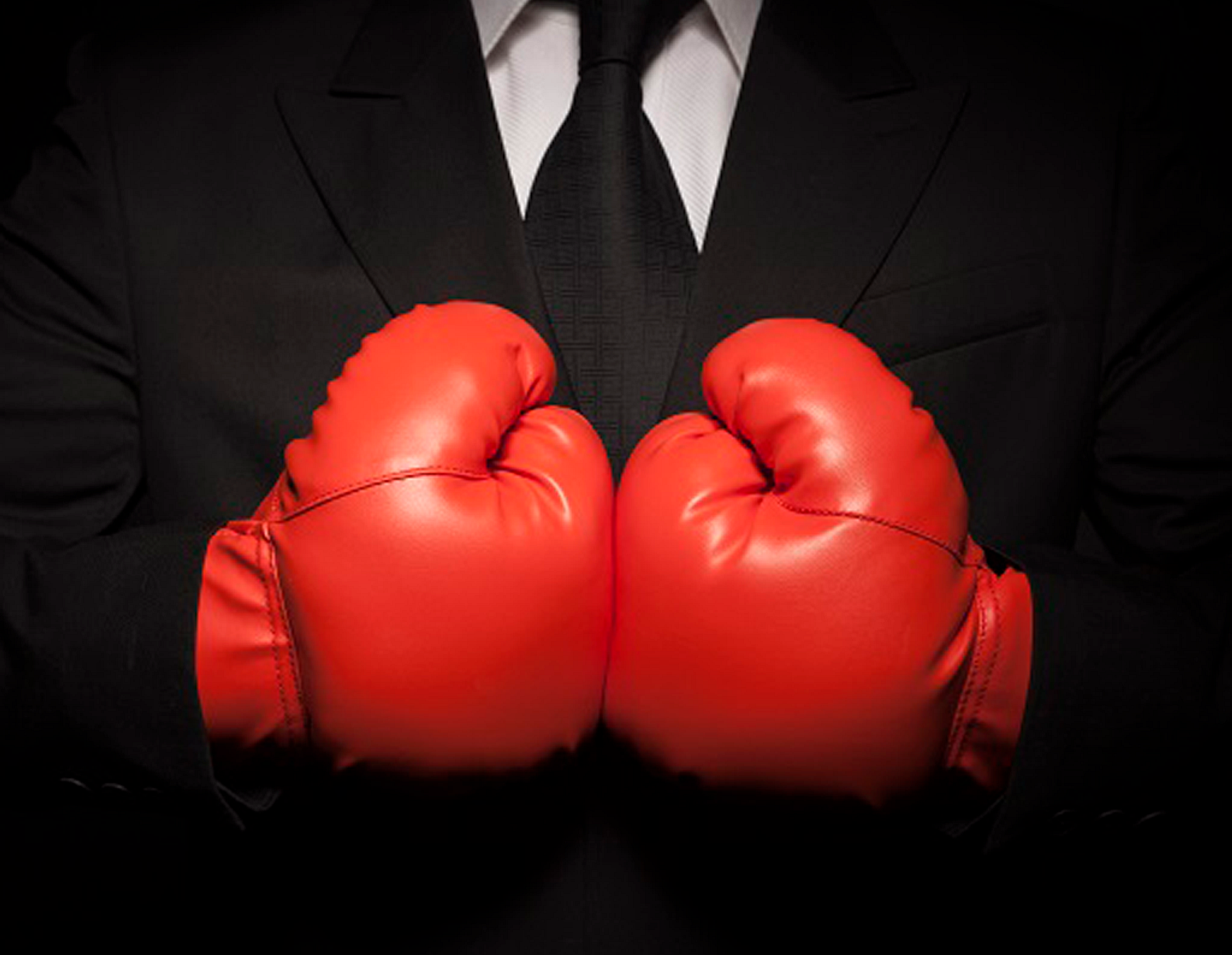 Man in black suit wearing red boxing gloves