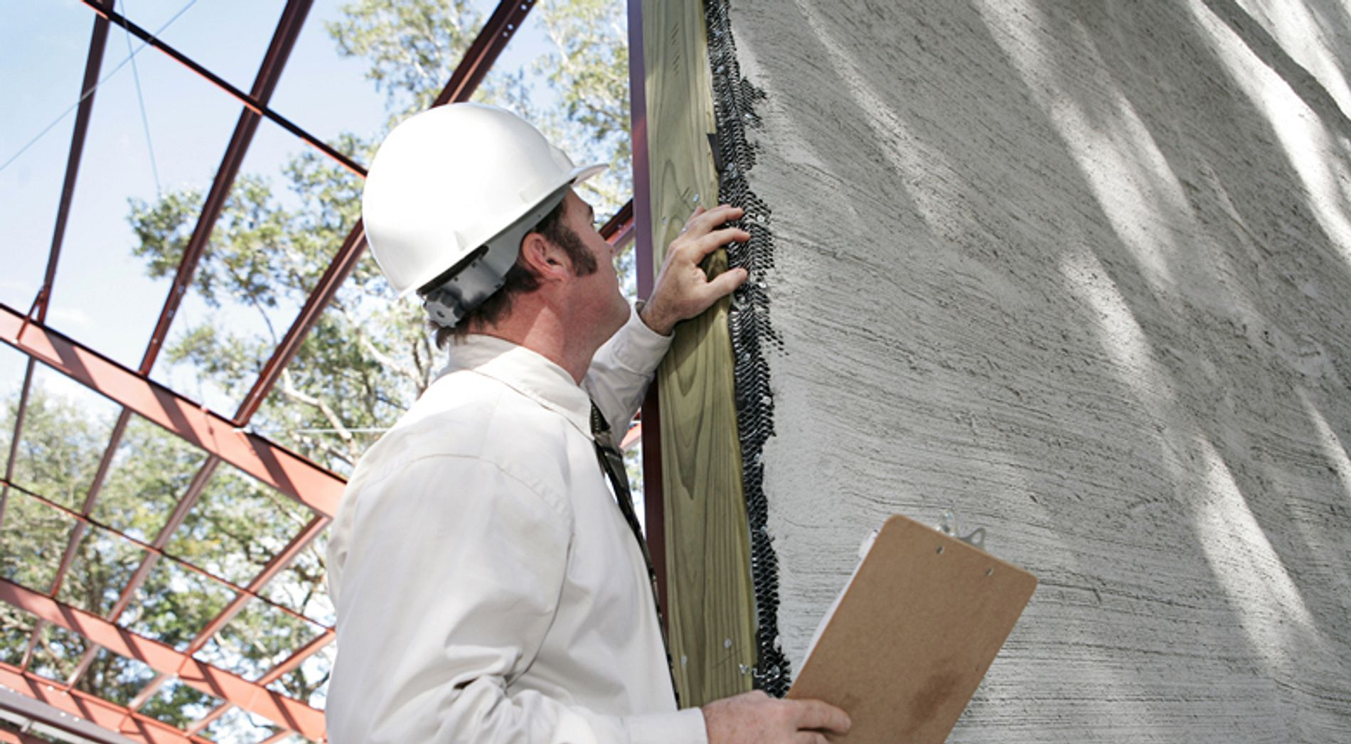 Man inspecting damage to a wall