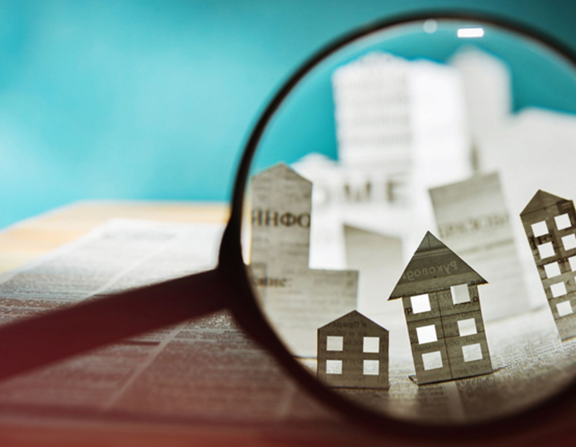Magnifying glass showing small homes cut from newspaper