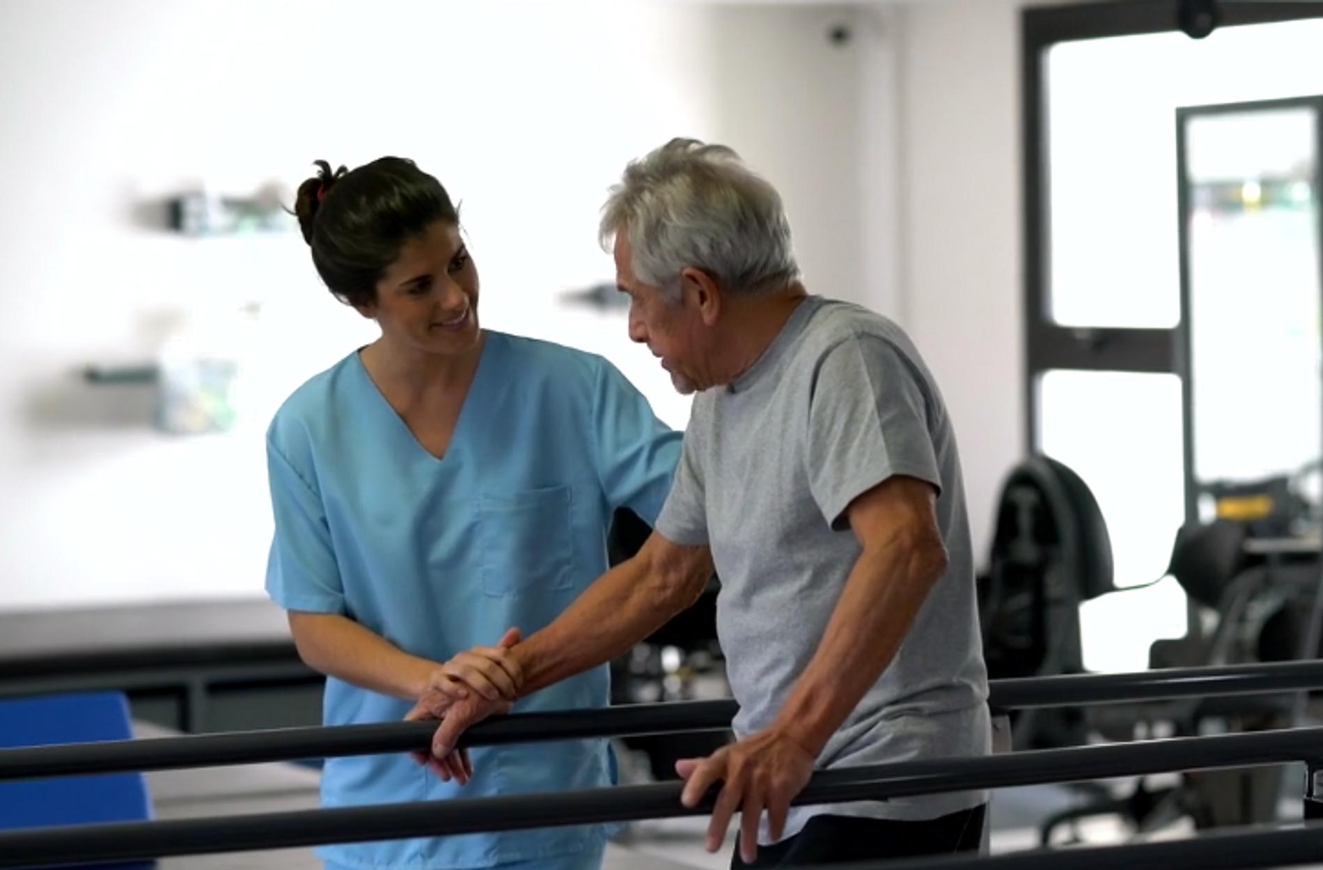 Nurse assisting a man in a rehabilitation facility
