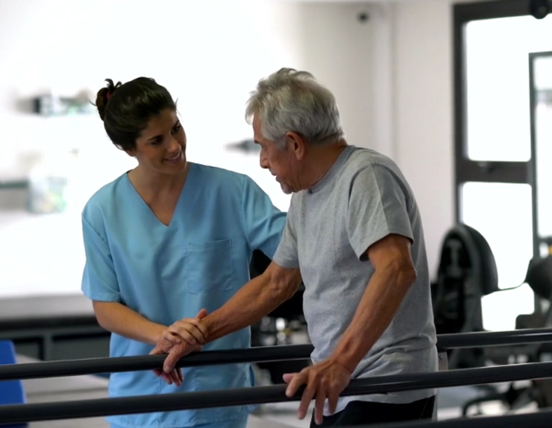 Nurse assisting a man in a rehabilitation facility