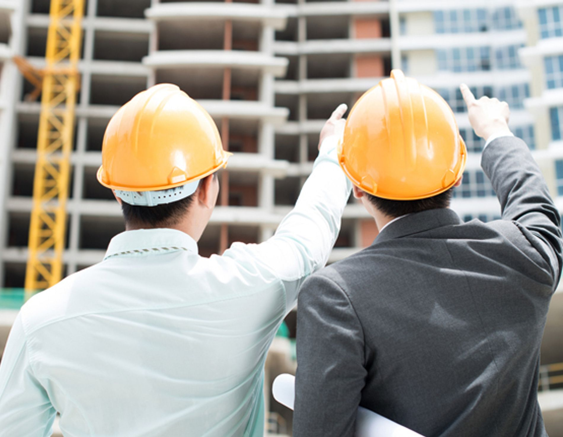 Two men on a construction site pointing upwards
