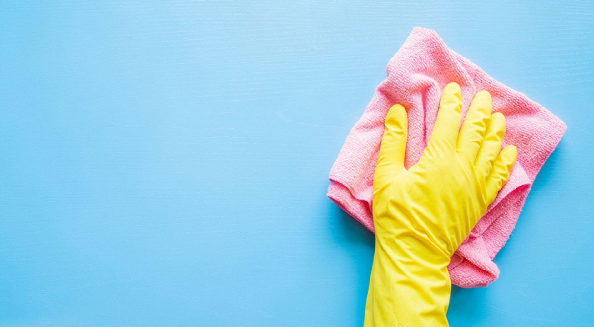 Hand in yellow glove wiping a counter with a towel
