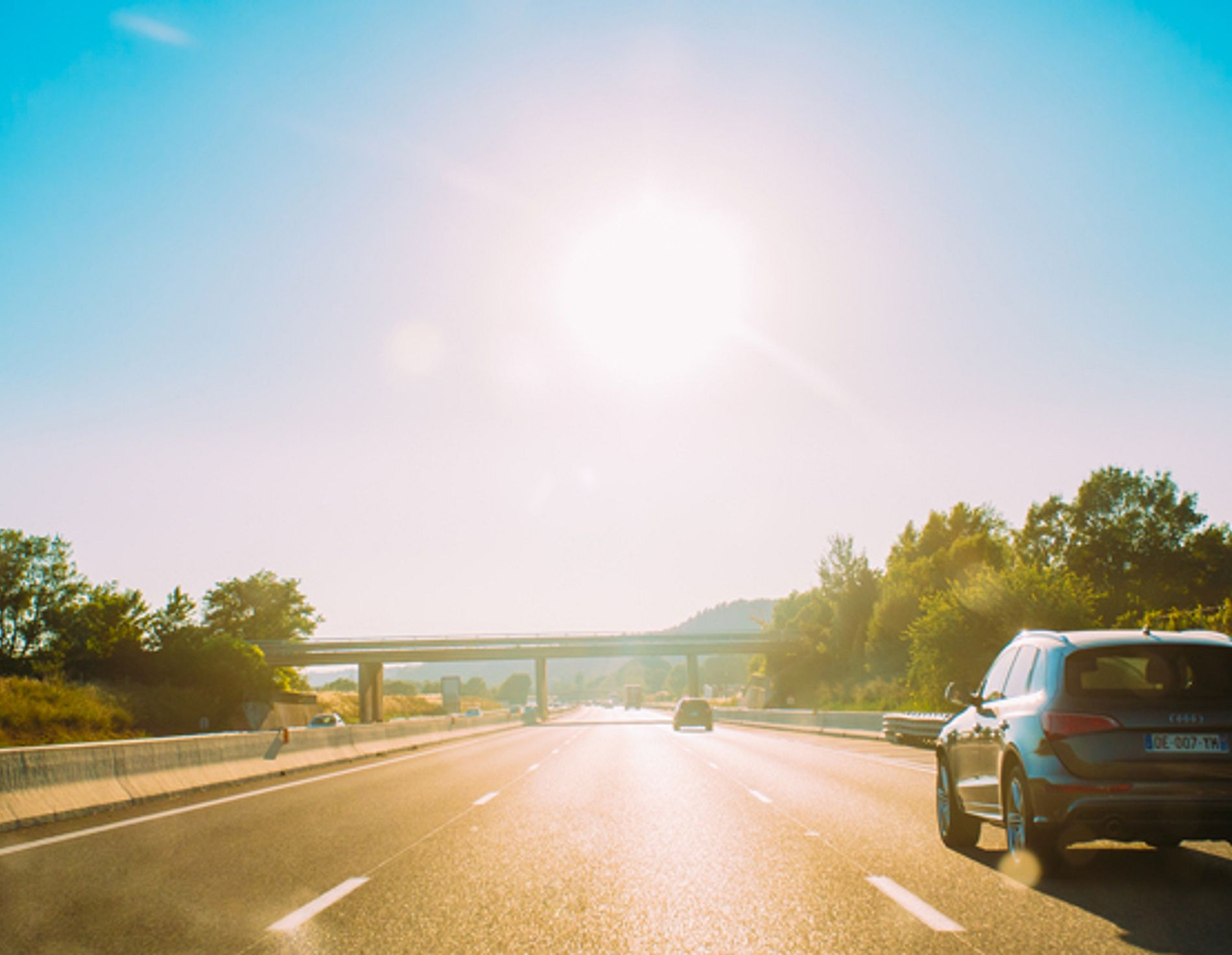 Cars driving down a sunny highway