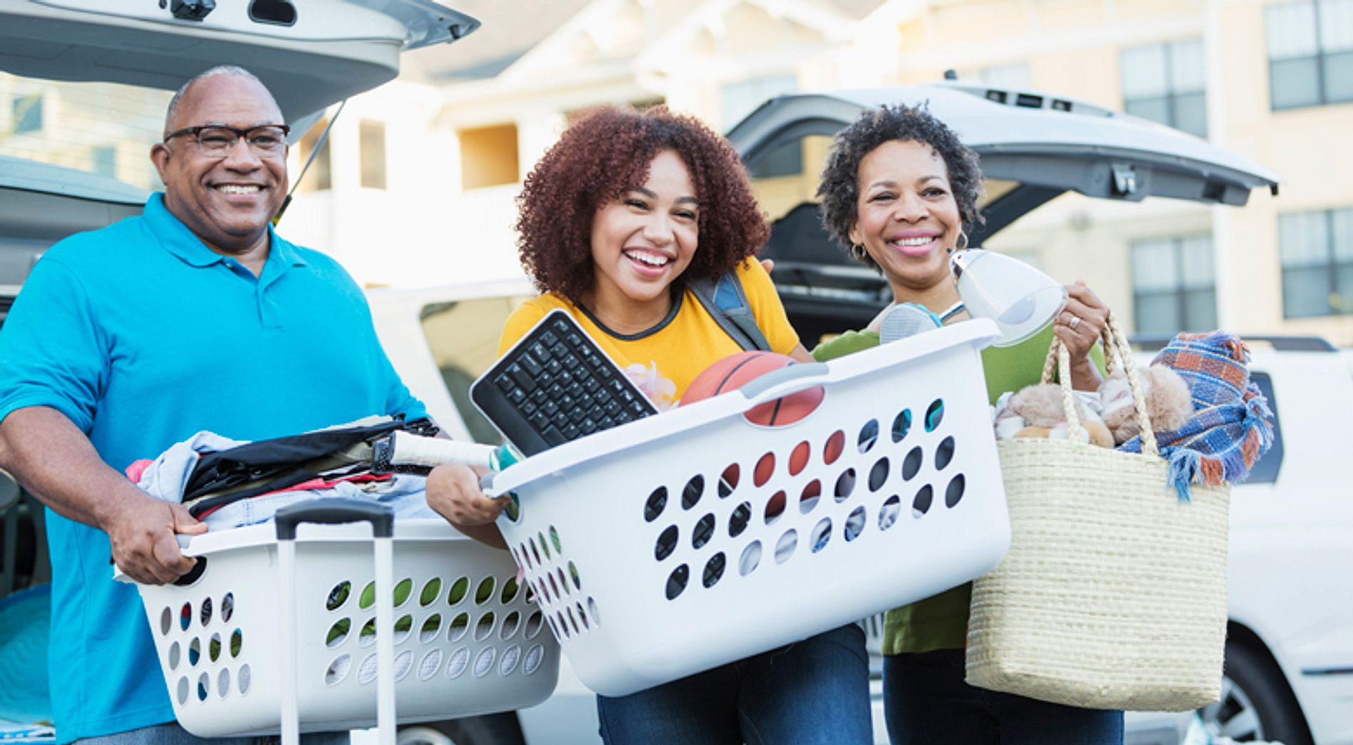 A family unloading baskets into a college dorm