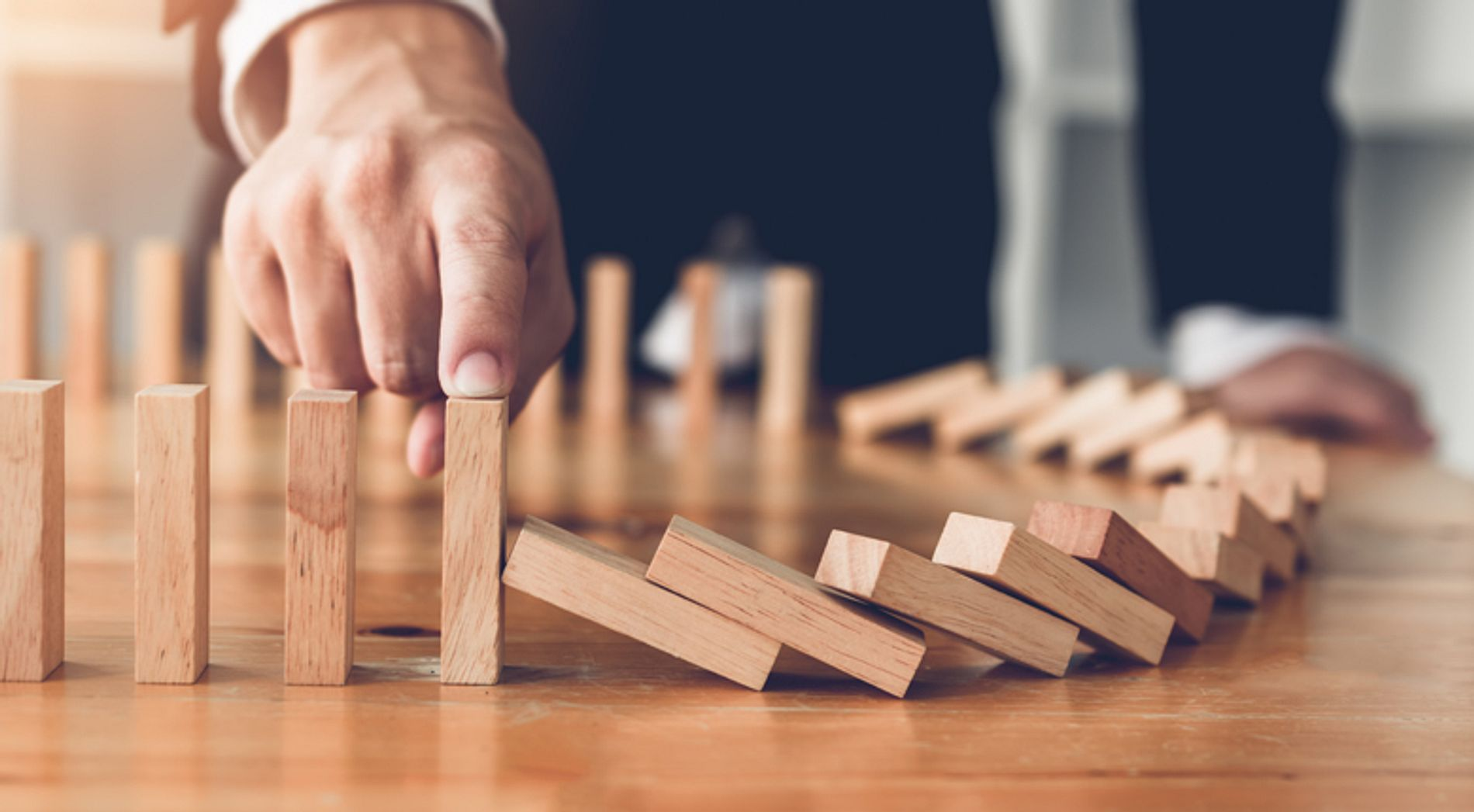 hand stopping dominoes from falling