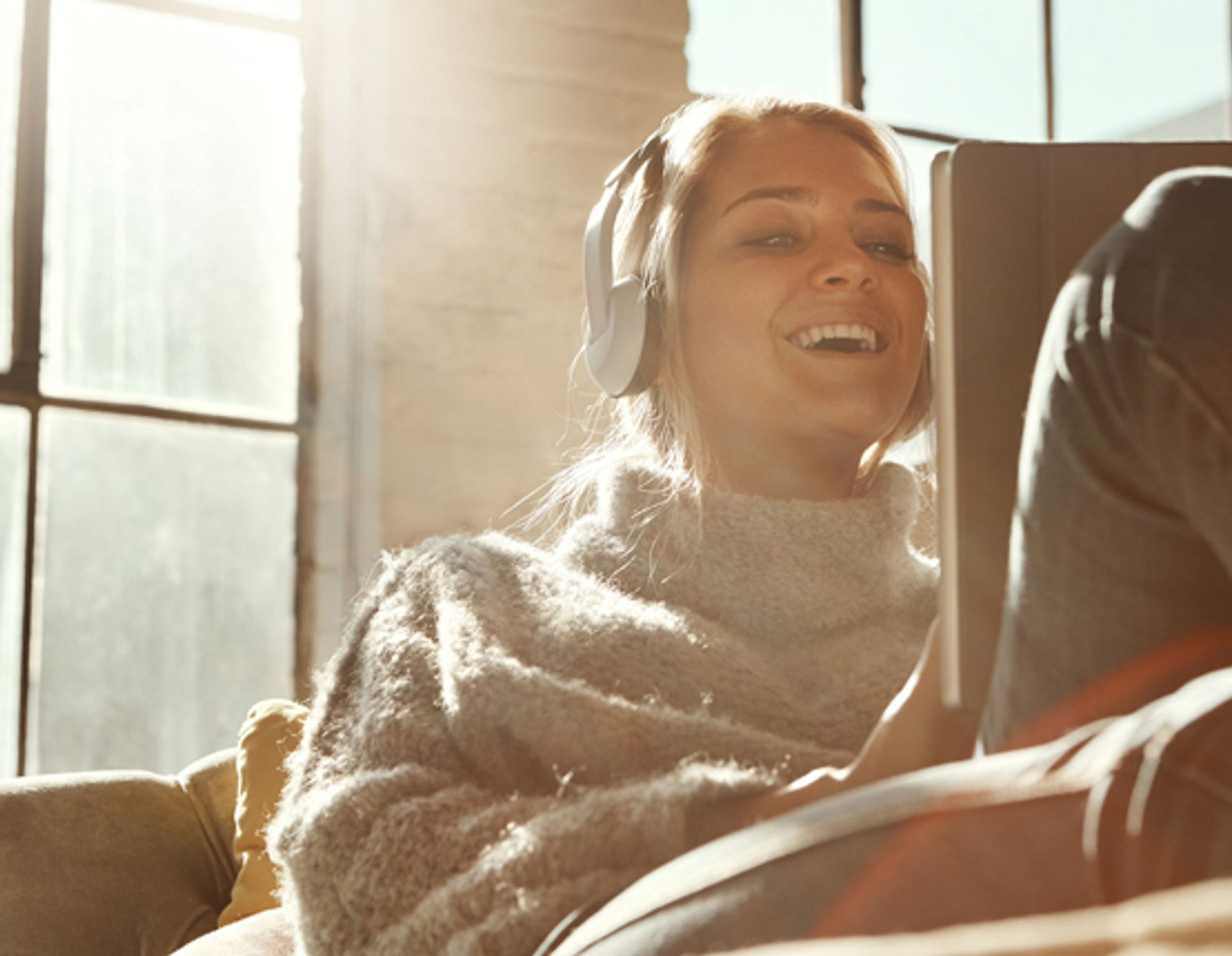 woman relaxing on the sofa and using headphones with a digital tablet