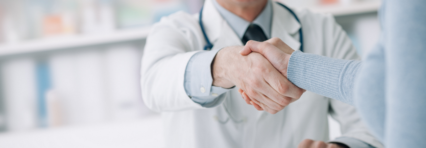 male doctor shaking hands with patient