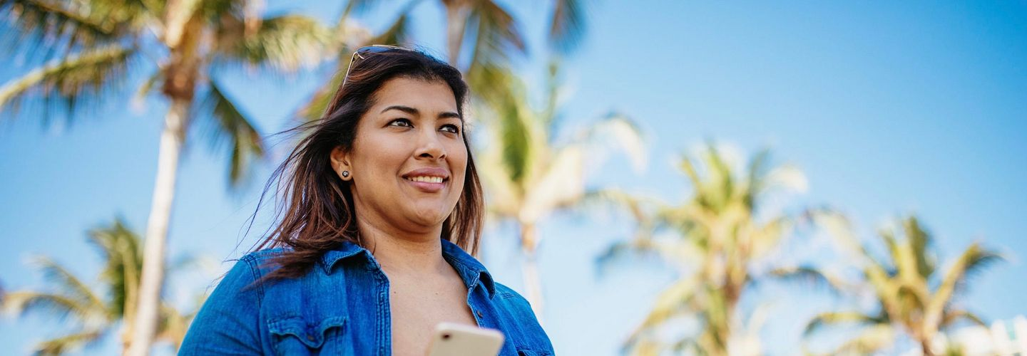 A Hispanic woman in her 30s holds her iPhone and wears her sunglasses on top of her head as she walks along with palm trees and an apartment building in the background. She has her earbuds in her hand. She's wearing a white T-shirt with an unbottoned, long-sleeved denim shirt over it with the sleeves rolled up.