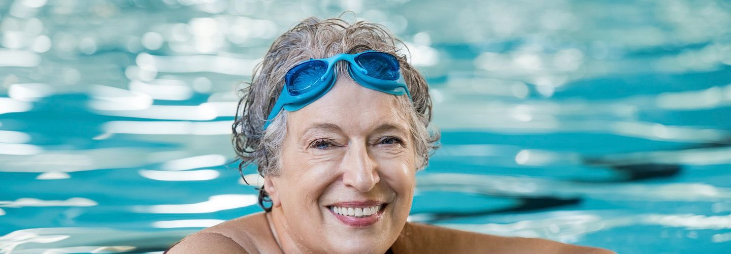 A senior woman crosses her arms over the edge of a pool. She is wearing goggles that are pushed up to the top of her forehead. She is smiling at the camera.