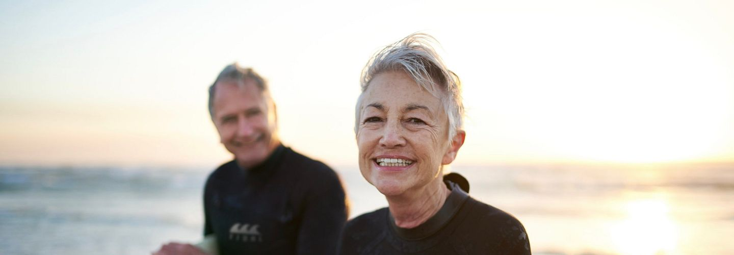 A couple in their 60s wearing wet suits with the ocean behind them. They are carrying surfboards.
