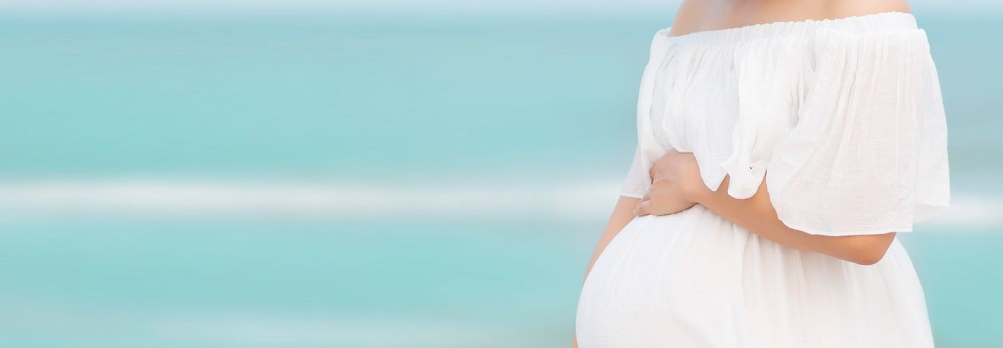 pregnant Asian woman in a strapless white dress holds one hand on top of her belly and supports it with her other hand while waling on the beach. She's looking down with her eyes closed and smiling. She is wearing a straw hat with a black band. The water is a beautiful shade of turquoise.