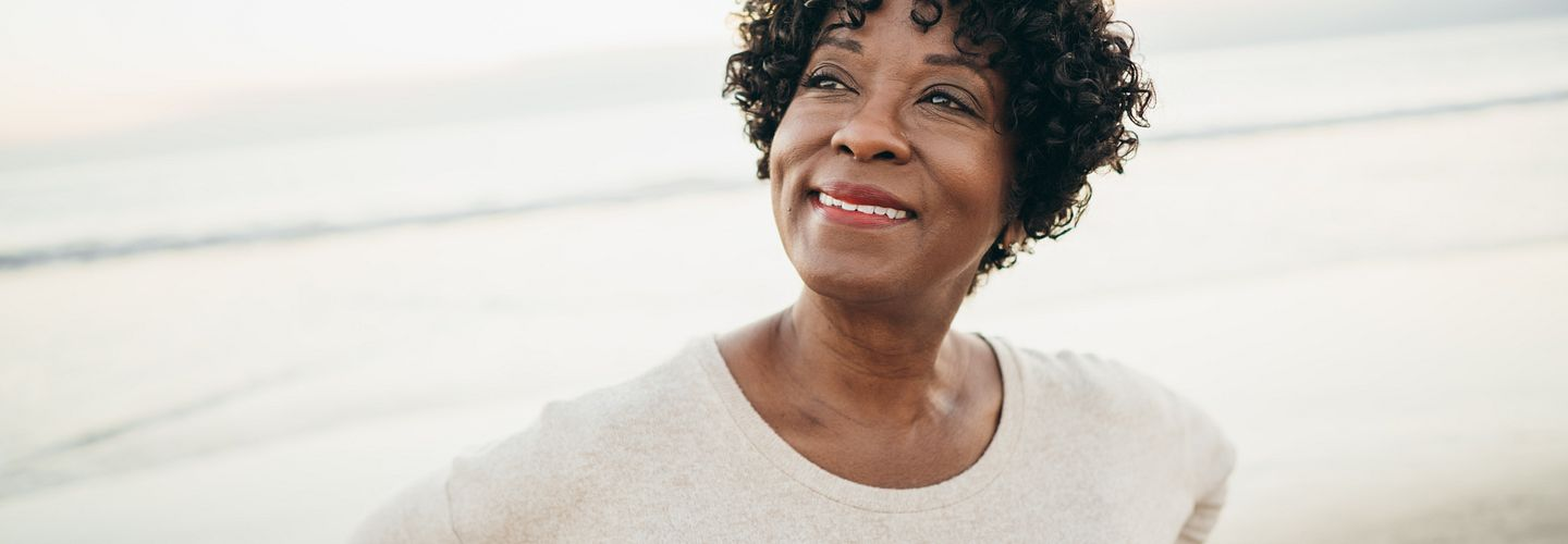 African American woman in her 50s or 60s standing on a beach smiling and looking off into the distance as she holds her hands against her lower back. She's wearing a light tan sweater.