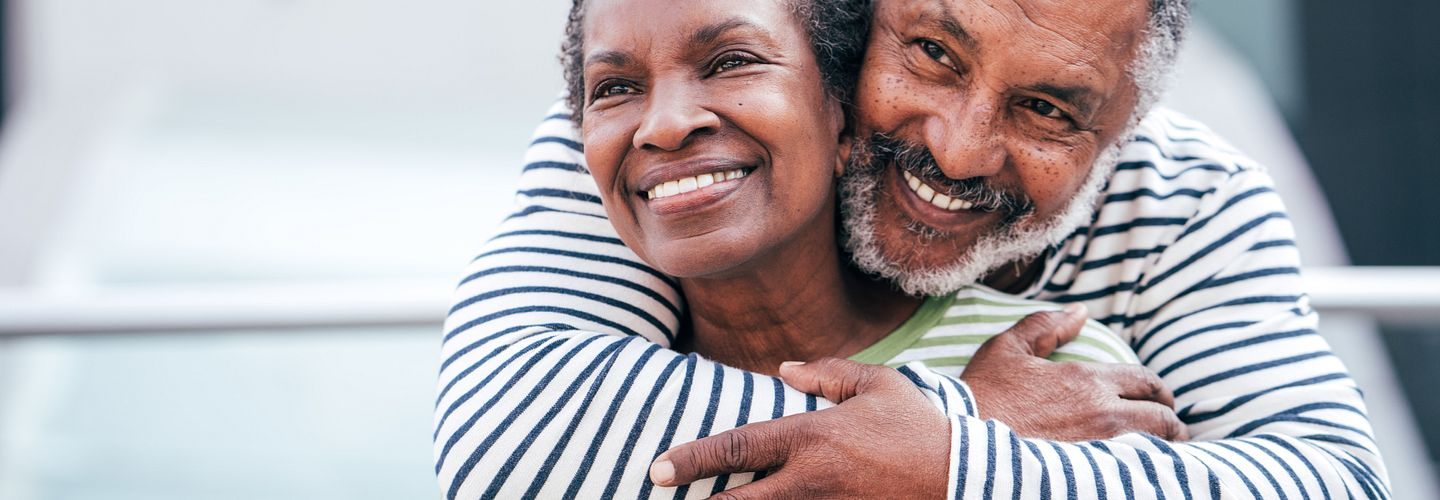 Senior African American couple in striped long-sleeve T-shirts smile as the man embraces the woman from behind. He has graying hair, and hers is still mostly brown.