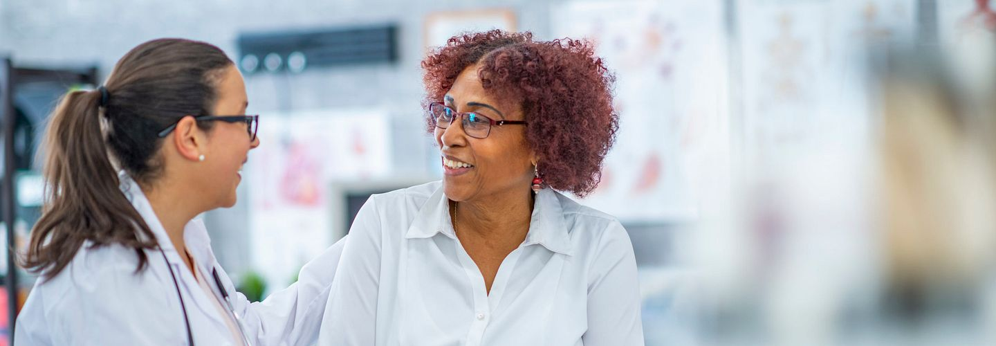 An African American woman with glasses and reddish-brown hair talks with a female health-care provider who is wearing a white coat and has a stethoscope draped over her shoulders. They are in a medical office setting with anatomical charts behind them. The background is blurred.
